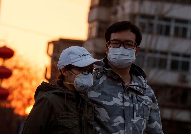 Çin başkenti Pekin'de koronavirüs önlemi olarak maskeyle dolaşan bir çift