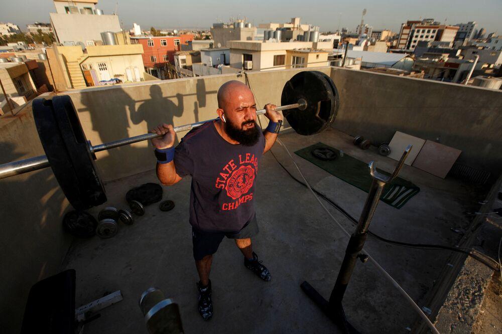 Irak'ın Erbil kentinde evinin çatısında antrenman yapan adam.