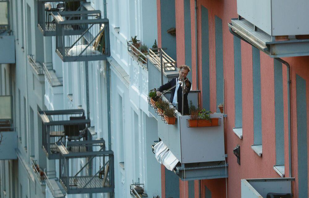 Almanya başkenti Berlin'de balkona çıkıp keman çalan adam.