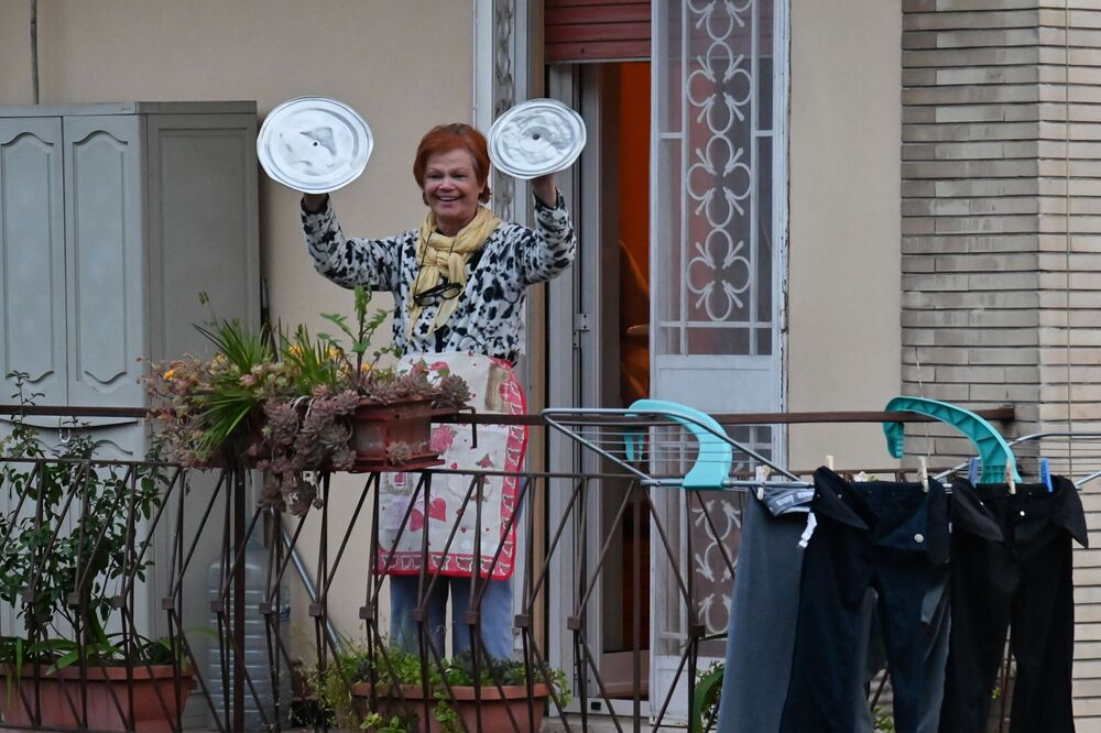Karantina altındaki İtalya'nın başkenti Roma'da başlatılan 'Look out from the window, Rome mine!' (Pencereden dışarı bak, Roma benim!) eylemine katılan bir kadın tencere kapaklarıyla müzik çalıyor. Eylemin amacı,  salgına karşı dayanışma içinde kalmak ve boşalan sokaklardaki sessizliği bozmak.