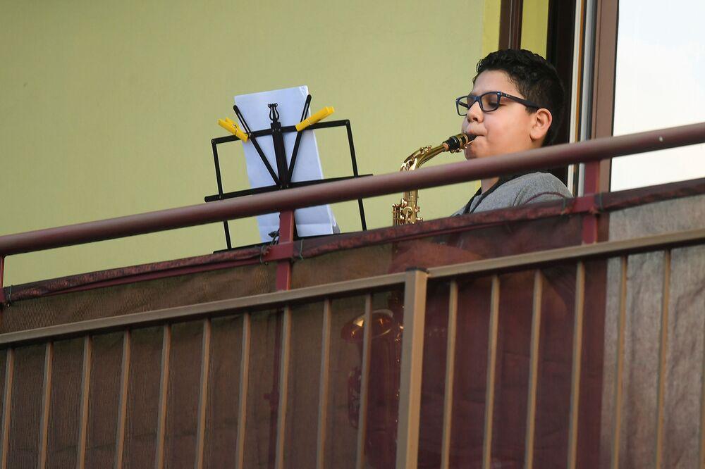 Milano'da bir çocuk evinin balkonunda saksafon çalıyor.