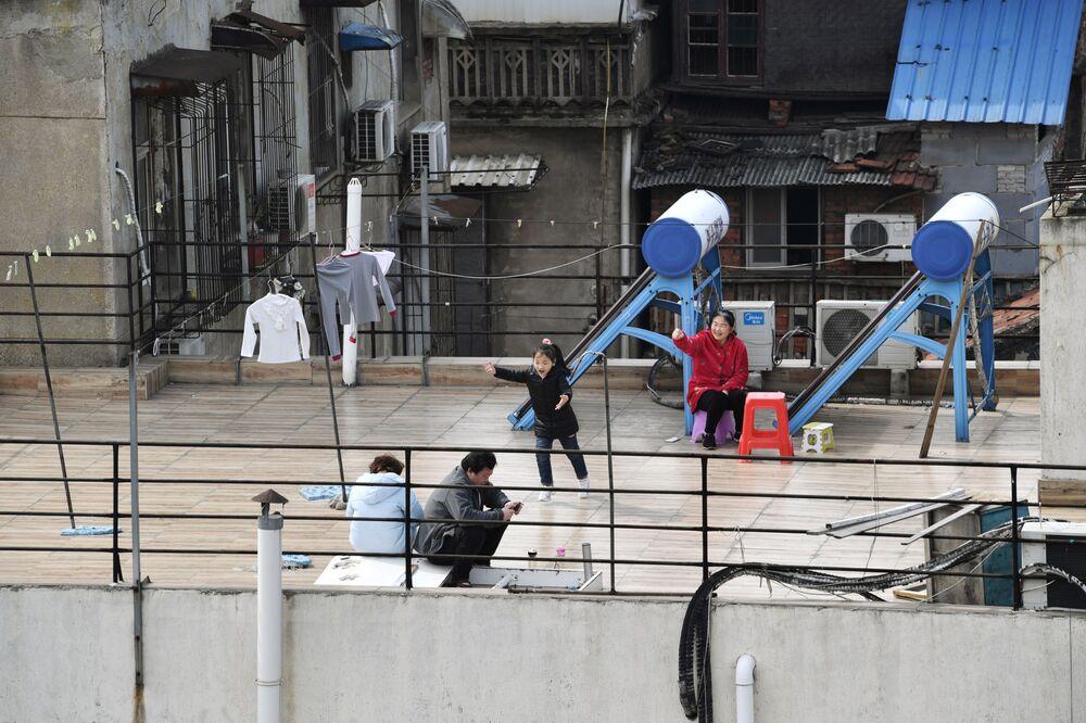 Çin anakarasında virüsün sıfır noktası olan Wuhan'da evin çatısında oturan insanlar