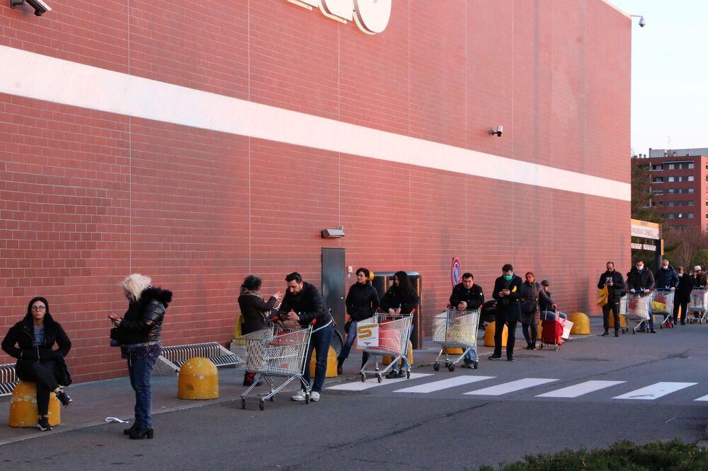 Neredeyse tüm marketlere aynı anda sadece birkaç kişinin girmesine izin veriliyor, geri kalanlar ise dışarıda sıra bekliyor. İnsanların birbirinden bir metrelik mesafede durması lazım, ama mümkünse 2-3 metrelik mesafe korumayı tercih ediyorlar.  Fotoğrafta: Milano'da marketin giriş kapısında sıra bekleyen insanlar.