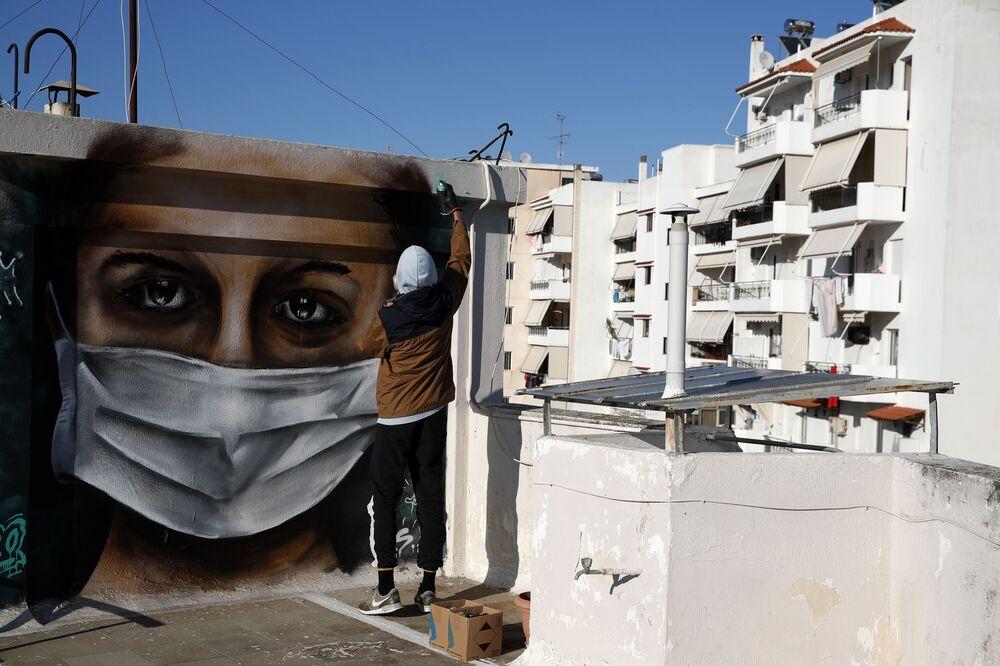 Yunanistan'ın başkenti Atina'da 16 yaşındaki sokak sanatçısı S.F. bir apartmanın çatısında koruyucu maskeli kadın resmini çizerek insanlara kendilerini koruma çağrısını yaptı.
