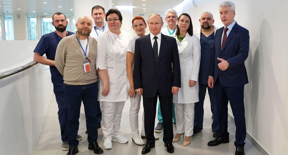 Rusya Devlet Başkanı Vladimir Putin ve Moskova Belediye Başkanı Sergey Sobyanin (sağda), Kommunarka'daki hastane çalışanlarıyla