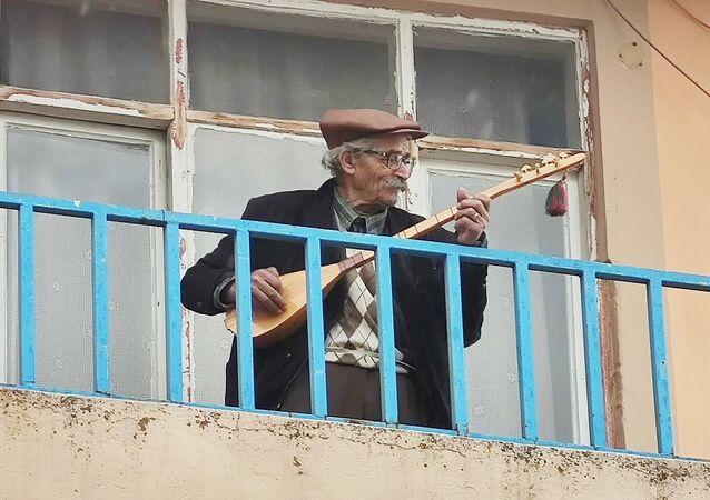 Tunceli'de 96 yaşındaki Hasan Tuncel, koronavirüs salgını nedeniyle cura ismi verilen çalgısını alarak evinin balkonuna çıkıp, türkü söyleyerek, 'Evde kalın' mesajı verdi.