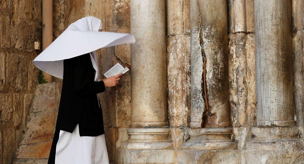 Kudüs'te Kutsal Kabir Kilisesi önünde dua eden bir rahibe