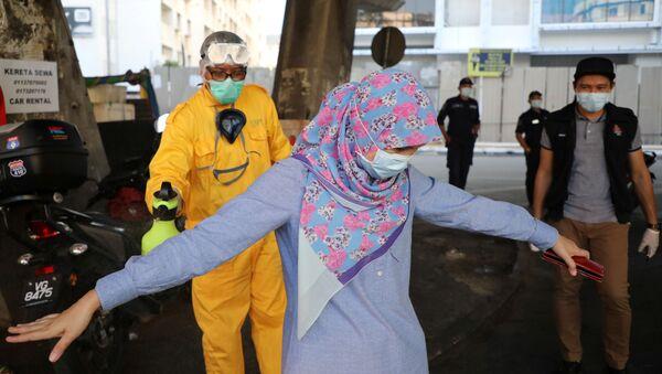 Koronavirüs önlemleri çerçevesinde sokakta dezenfekte edilen bir kadın, Kuala Lumpur, Malezya - Sputnik Türkiye