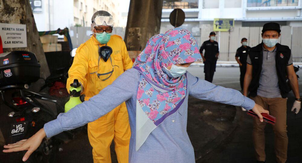 Koronavirüs önlemleri çerçevesinde sokakta dezenfekte edilen bir kadın, Kuala Lumpur, Malezya