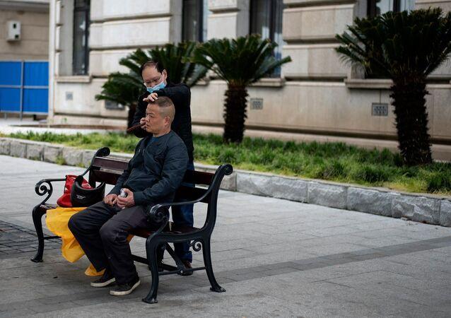 Vuhan kentinde maske takan bir berber bankta bir müşterinin saçını kesiyor.