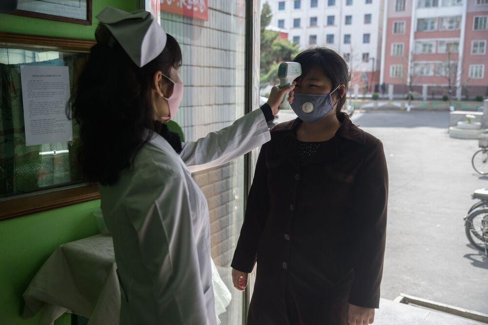Bir  sağlık çalışanı, başkent Pyongyang'daki hastane girişinde bir kadının ateşini ölçerken
