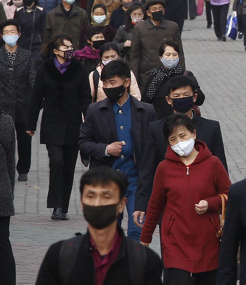 Koruyucu maskeli Kuzey Koreliler, başkent Pyongyang sokaklarında.