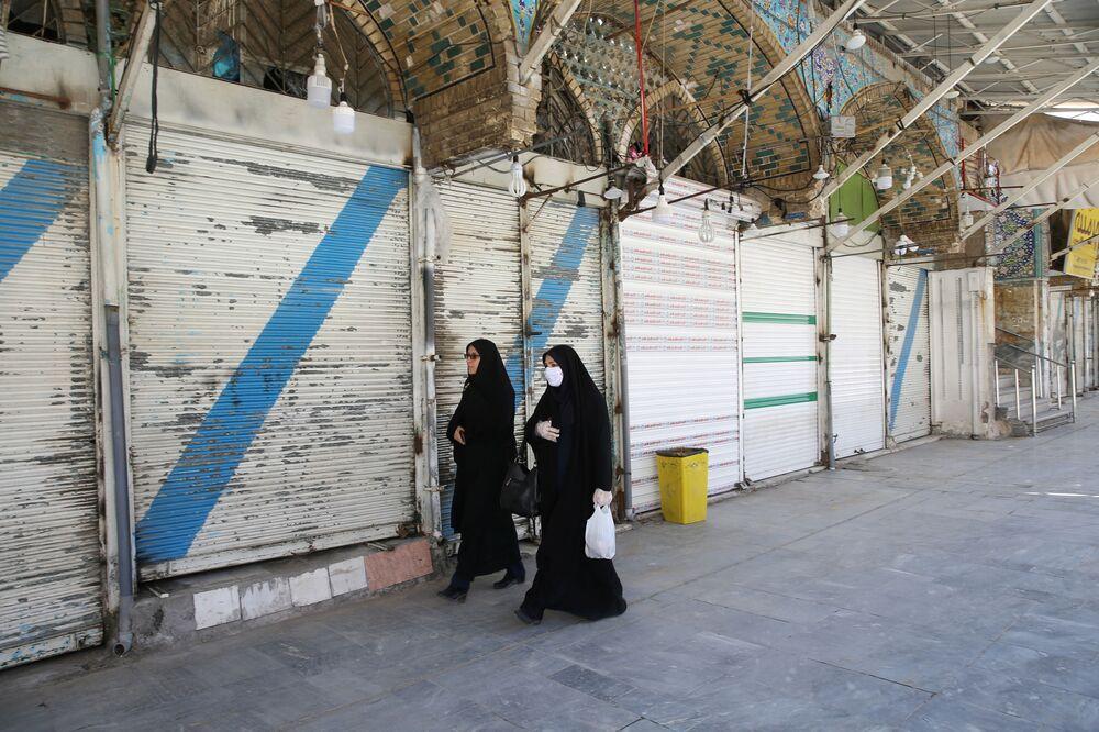 İran'ın Kum kentinde dükkanların kapalı olduğu sokaktan geçen maskeli ve eldivenli kadınlar.