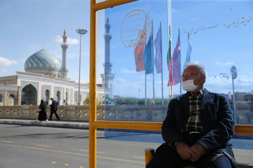 İran'ın Kum kentinin maskeli sakini durakta otobüs beklerken
