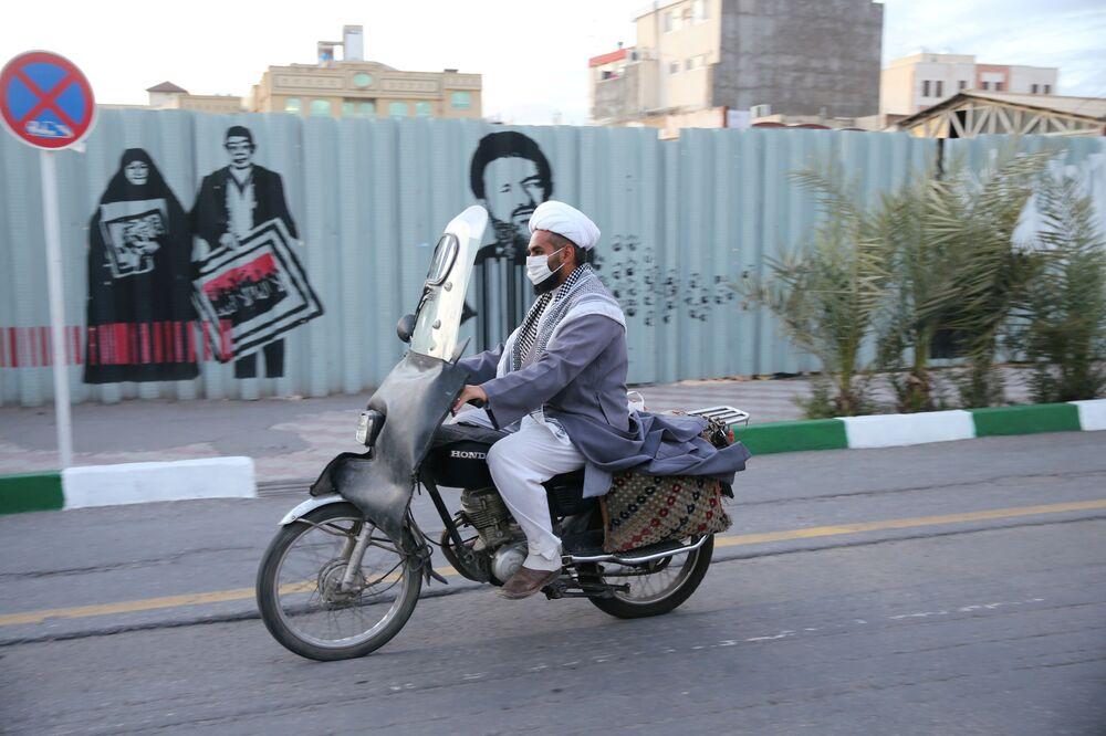 Koruyucu maskeli İran vatandaşı motosiklet kullanırken