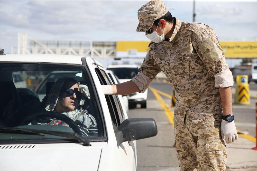 İran'da Kum kentinin girişinde güvenlik güçleri sürücülerin ateşini ölçüyor.