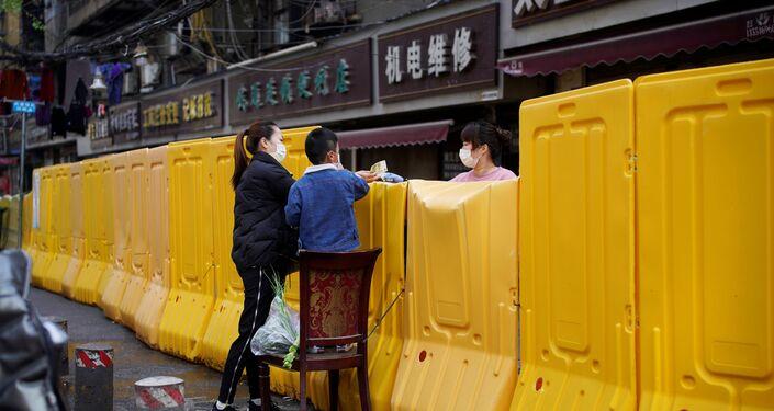 Koronavirüs salgının başlangıç noktası olan Çin'in Hubei vilayetinde bulunan Vuhan kentinde bariyerler üzerinden alışveriş yapan kent sakinleri