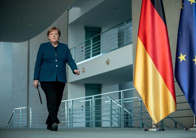 Angela Merkel, kendini karantinaya almadan önce 22 Mart'ta başbakanlık binasında koronavirüs basın toplantısına giderken