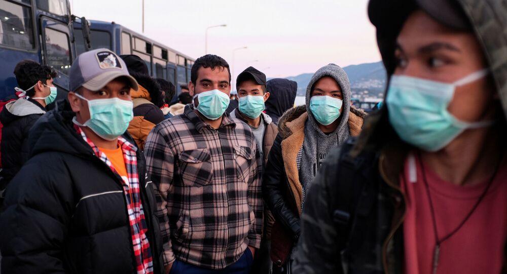 Yunanistan'da tutulan ve koronavirüs önlemi olarak maske takan göçmenler, Midili Adası'nda kendilerini anakaraya nakledecek feribotu beklerken