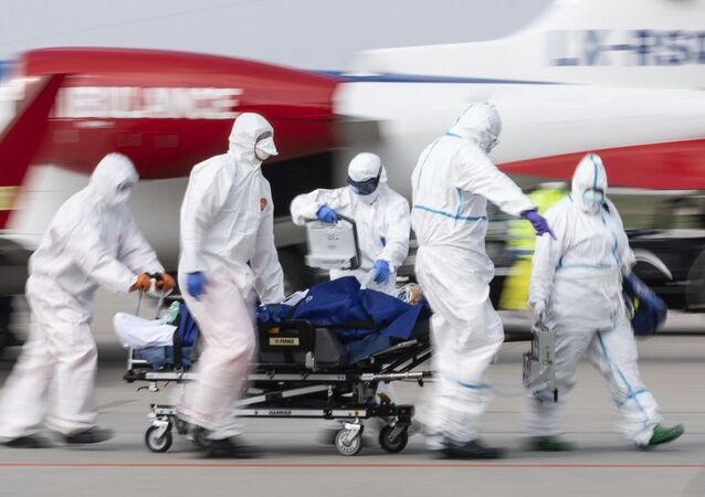 A patient from France who is seriously ill with the coronavirus is transported from an ambulance plane after landing at Dresden International Airport in Dresden, Germany