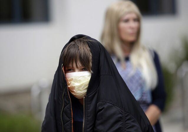 A young worshipper wears a mask while lined up to take communion on Palm Sunday outside of Godspeak Calvary Chapel Sunday, April 5, 2020, in Newbury Park, Calif. Many churches, beaches, parks and hiking trails around the state have been closed because they attracted large crowds amid the coronavirus outbreak. (AP Photo/Marcio Jose Sanchez)