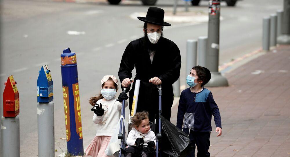 İsrail'de koronavirüsün en çok vurduğu yer olan ve karantinaya alınan Bnei Brak'ta maskeli dolaşan bir ultra-Orthodoks Yahudi aile