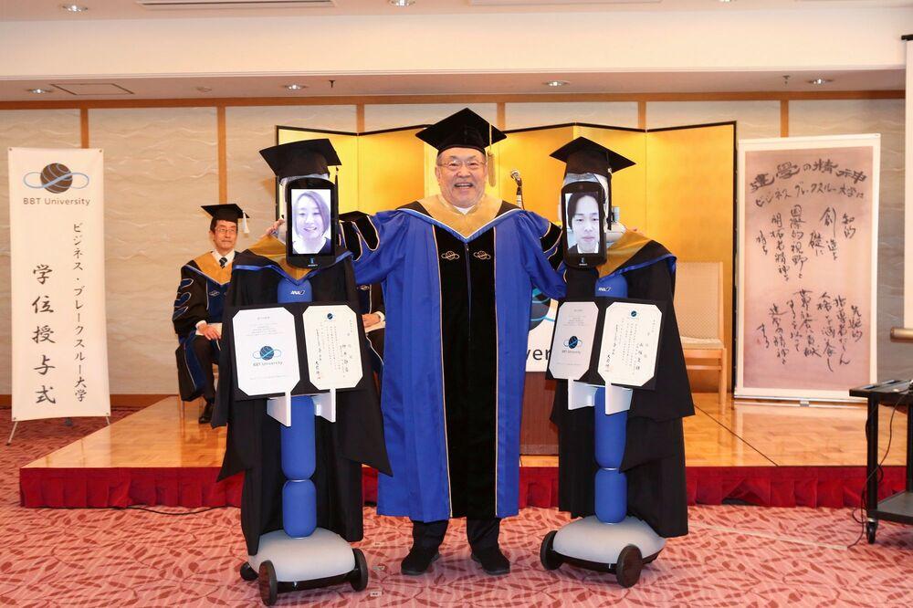 Robotun yüz kısmındaki tablet üzerinde görüntüleri yer alan öğrenciler, mezuniyet elbisesi giydirilmiş robotlar aracılığıyla sırasıyla üniversite yetkililerinden diplomalarını aldı.