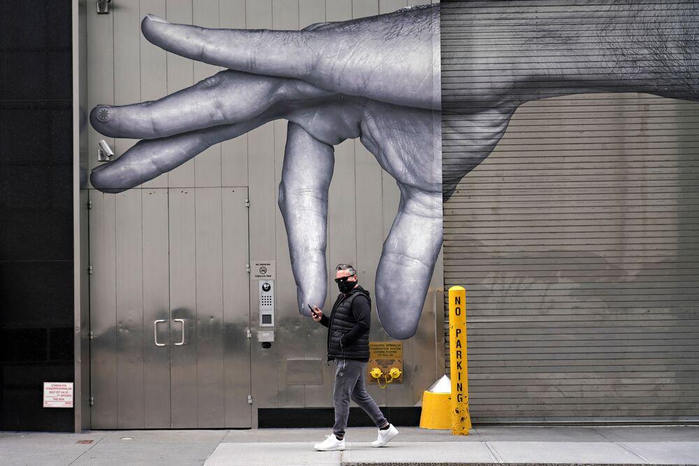 ABD'nin New York kentinde bir duvar resmi yanından geçen  maskeli adam