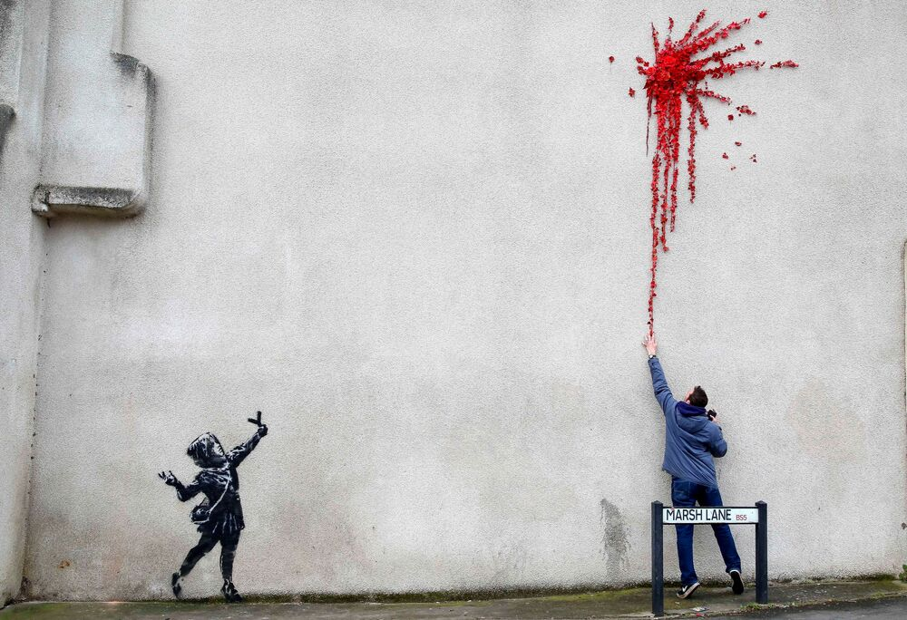 Bir adam, İngiltere'nin Bristole kentindeki ünlü ressam Banksy'nin eserinin yanında poz verirken