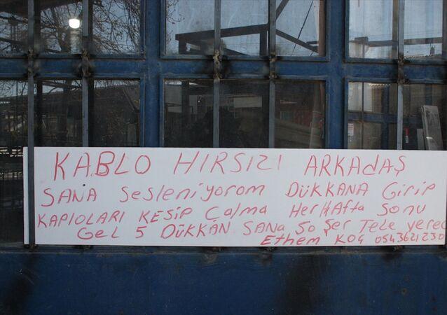 Edirne'nin Keşan ilçesinde sanayi sitesindeki iş yerlerinden 6 kez hırsızlık yapılan esnaf, kapının üzerine Kablo hırsızı arkadaş, dükkana girip kabloları kesip çalma. Her hafta sonu gel, 5 dükkan sana 50'şer lira vereceğiz. yazılı kağıt astı.