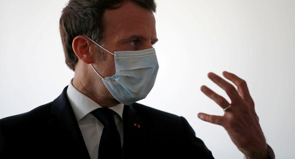 Emmanuel Macron koruyucu maske takmış halde sağlık çalışanlarıyla konuşurken, Pantin, Paris, Fransa