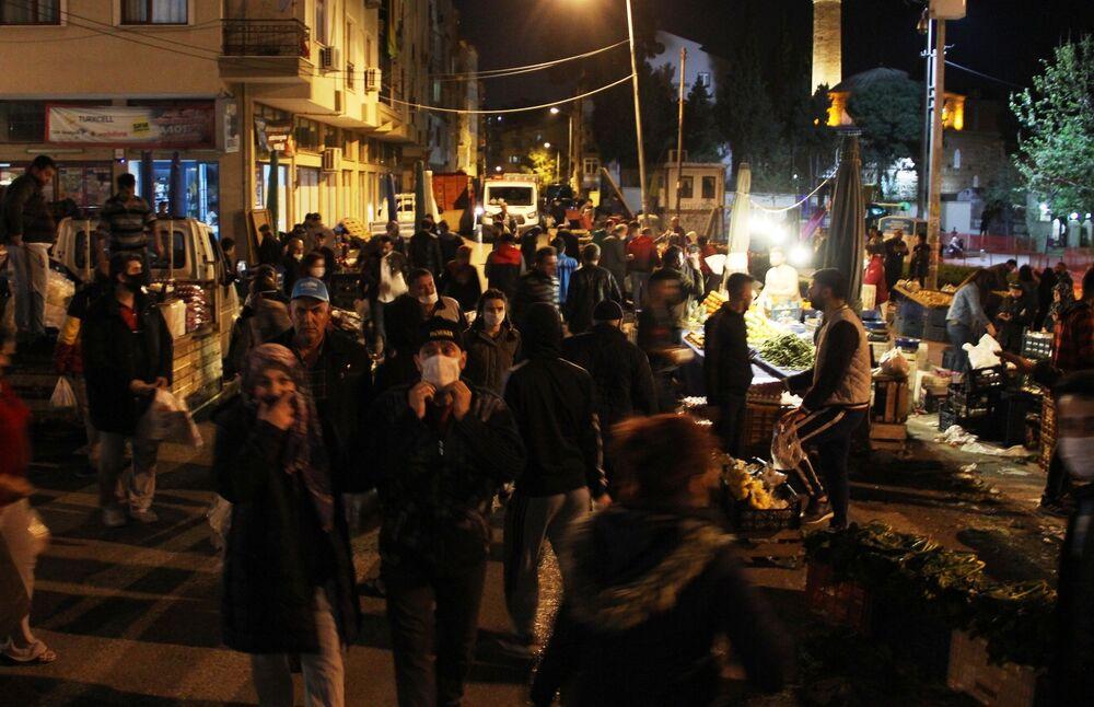 Manisa'da gece saatlerinde kurulan Cumartesi pazarına akın eden vatandaşlar, sosyal mesafe kurallarını ihlal ederek alışveriş yaptı.