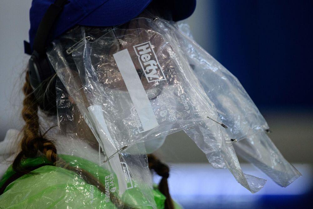 Hong Kong Havalimanı'nda görüntülenen maske ve plastik poşetleri takan bir kadın.