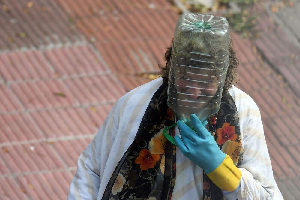 Uruguay'da plastik  pet şişe takarak kendini koronavirüsten korumaya çalışan bir kadın.