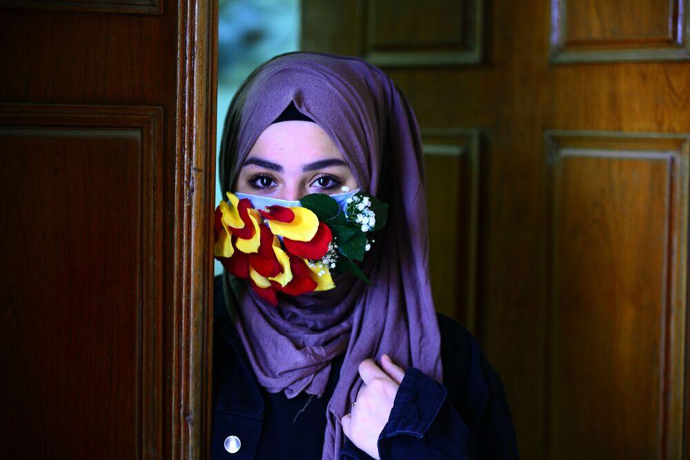 Çiçeklerin yapraklarıyla süslü maske takan İranlı kadın.
