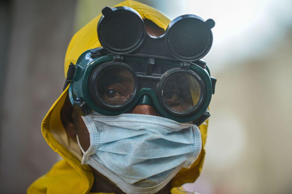 Etiyopya'da koruyucu maske ve gözlük takan temizlik şirketinin çalışanı.