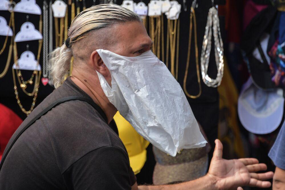 Brezilya'nın Sao Paolo kentinde  plastik poşeti maske olarak kullanan bir sokak satıcısı.