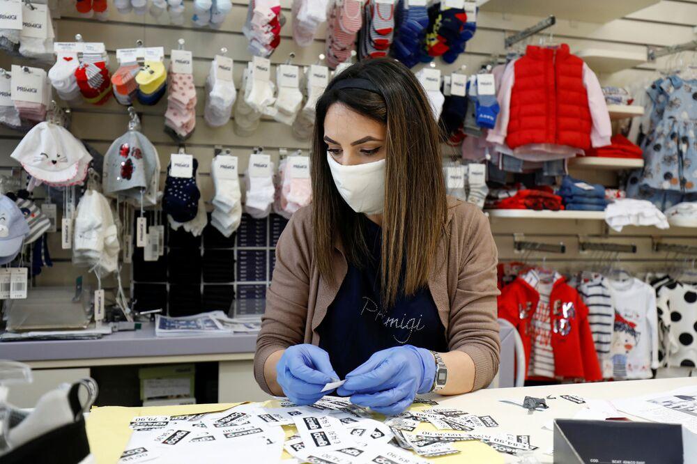 İtalya'nın Katanya kentinde açılmasına izin verilen bebek ve çocuk mağazalarından birinin maskeli ve eldivenli satıcısı