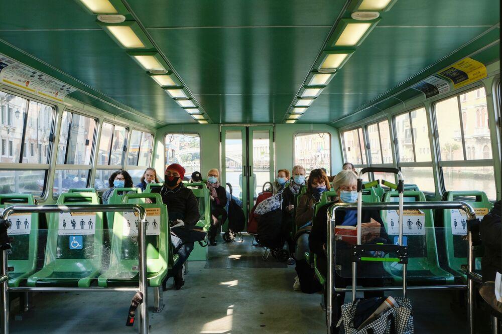 İtalya'nın Veneto kentinde faaliyet gösteren deniz otobüsünün maskeli yolcuları.