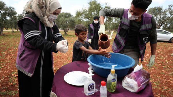 Suriye-Gönüllüler, koronavirüs tedbirleri kapsamında mültecilere ellerini nasıl yıkayacağını öğretiyor. - Sputnik Türkiye