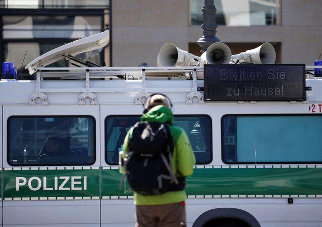 Evde kal yazısıyla devriye gezen bir polis aracı, Brandenburg Kapısı, Berlin, Almanya