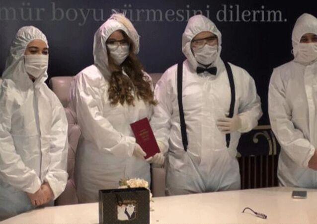 Koronavirüs salgını nedeniyle düğünü ertelenen sağlık çalışanı Cemre Yetgin ve Yunus Taştemür çifti, gelinlik ile damatlık yerine koruyucu tulumlarını giyip nikah masasına oturdu