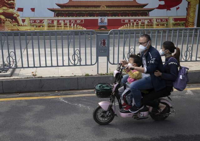 Residents wearing masks pass by government propaganda posters featuring Tiananmen Gate in Wuhan.