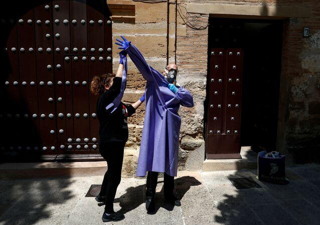 Rahip Andres Conte, yoksullara yardım dağıtmaya başlamada önce ikiz kardeşi Inma'nın yardımıyla koruyucu ekipmanları giyiyor.