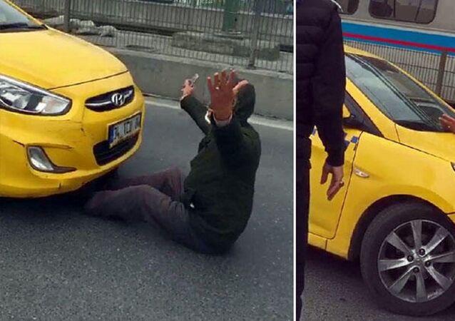 Bunun üzerine koşarak taksinin önünü kesen kişi, bir süre taksici ile tartıştı. Önünde yatarak taksinin gitmesine izin vermeyen kişi, trafiğin durmasına neden oldu.