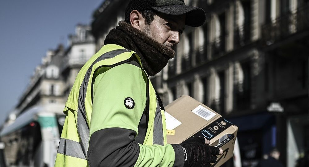 A delivery man crosses a street as he delivers an Amazon package in Paris on March 19, 2020, on the third day of a strict lockdown in France to stop the spread of COVID-19, caused by the novel coronavirus.