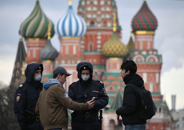 Police officers wearing protective face masks check a digital pass to the movement during the mandatory self-isolation amid coronavirus disease outbreak at Red Square, in Moscow, Russia.