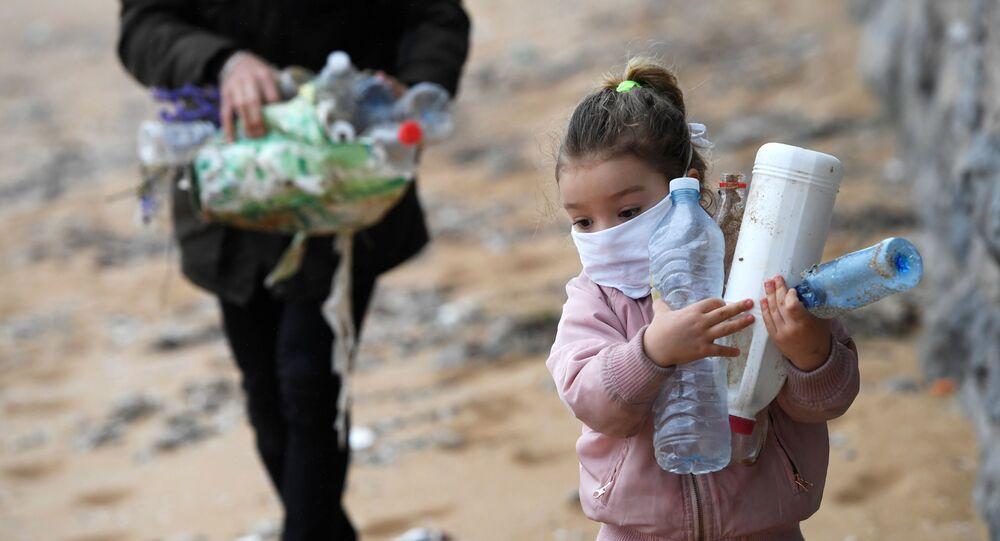 İspanya'da koronavirüs nedenli çocuklara sokağa çıkma yasağının 6 hafta sonra ilk kez kısmen kalkmasının ardından Gijon kentinde sahildeki plastik çöpleri temizleyen baba-kız