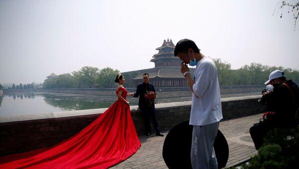 Çin - 720 bin metrekarelik alanı kaplayan ve ülkedeki saraylar arasında en bilineni olan ''Yasak Şehir dışında bir çift düğün fotoğraflarını çektiriyor. - Sputnik Türkiye