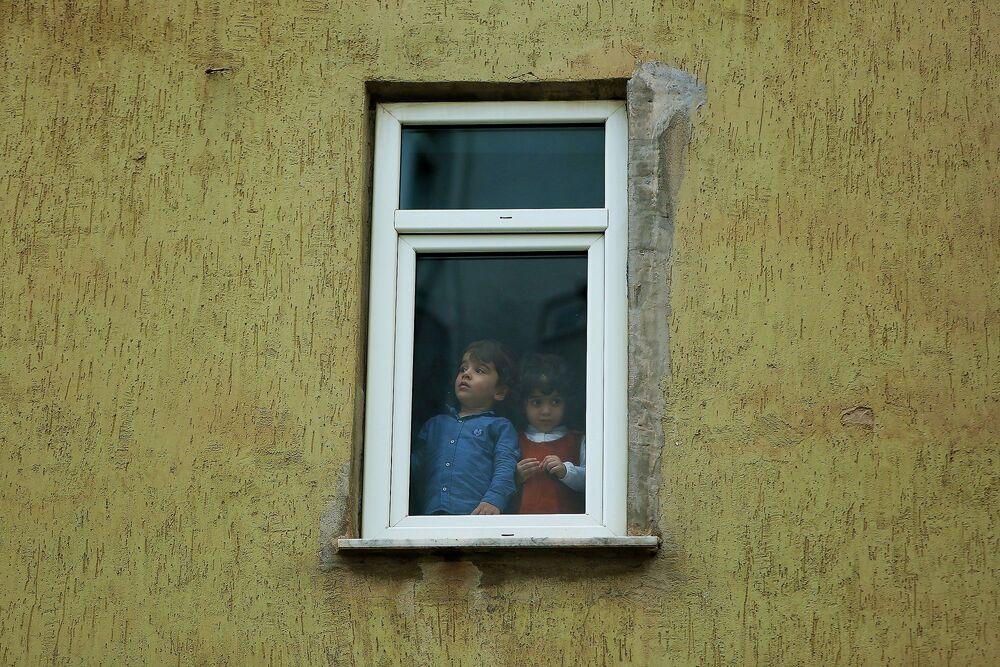 Evlerinin penceresinden boş sokakları seyre dalan çocuklar